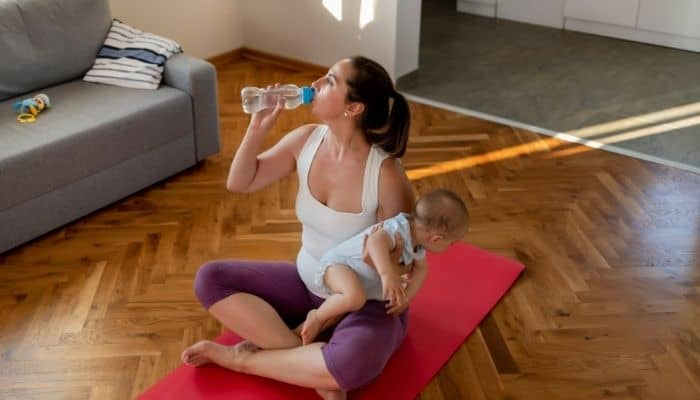 New mom exercising with a baby in her lap and drinking water