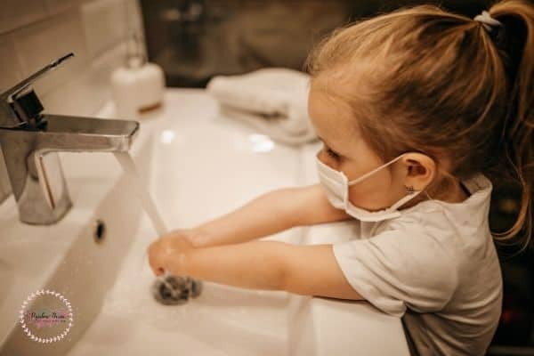 A toddler girl washing her hands.